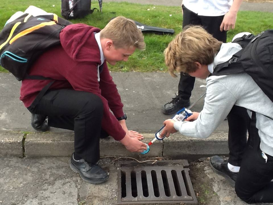 pupils sticking yellow fish on to kerb